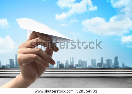 Human hand holding paper plane ready to launch - stock photo
