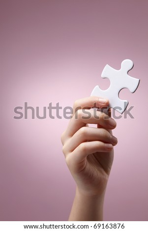 Human hand holding puzzle piece. - stock photo