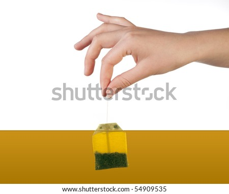 Human hand holding tea bag