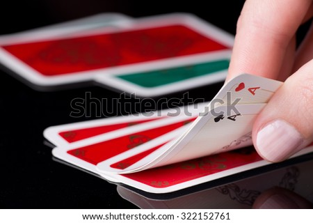 Human hand holding two aces in poker game, cards in background - stock photo