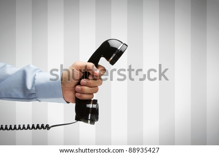 Human hand holding vintage telephone with copy space - stock photo