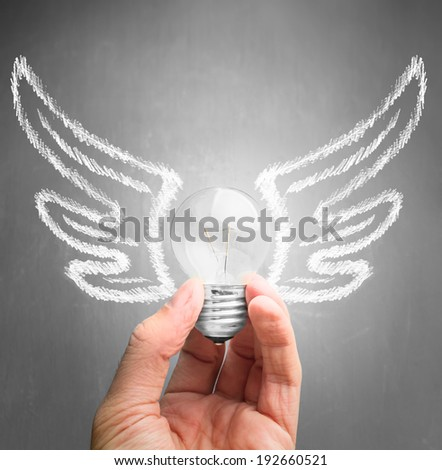 Human hand holds a light bulb with drawing wings, concept of new idea and inspiration - stock photo