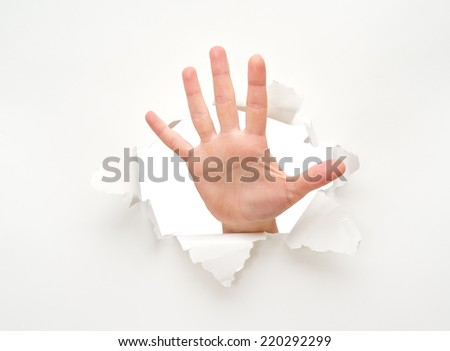 human hand in a hole in a white empty paper poster - stock photo