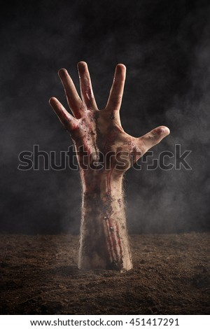 Human hand in blood and dirt on dark background - stock photo