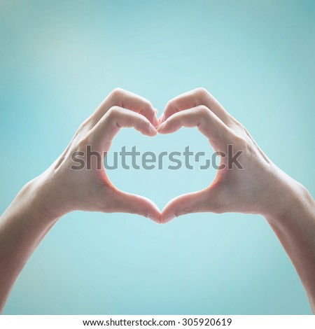 Human hand in heart shape showing love and friendship on blurred blue sky with clouds background in vintage color tone: Peace, kind and humanitarian concept/ campaign/ idea in retro style toned colour
