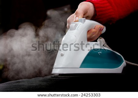 Human hand in red sleeve holding steaming iron over black - stock photo