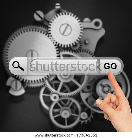 Human hand indicates the search bar in browser. Metal gears as backdrop - stock photo