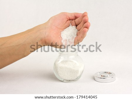 human hand is strewing salt into a glass jar - stock photo
