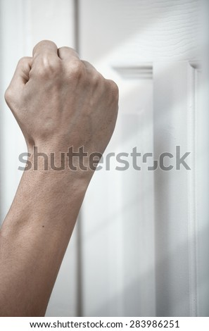 Human hand knocking at the wooden door - stock photo