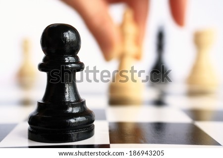 Human hand moves a chess piece on a chess piece pawn background closeup. - stock photo