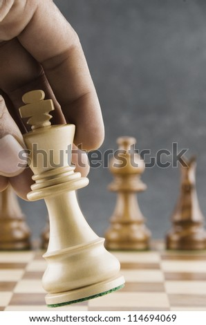 Human hand moving a king chess piece - stock photo