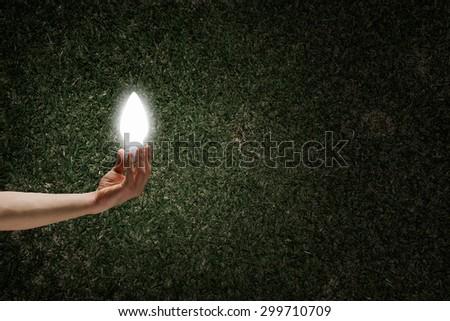 Human hand on dark background holding light bulb - stock photo