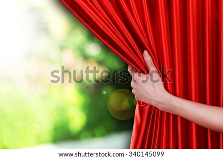 Human hand opens red curtain on nature background - stock photo