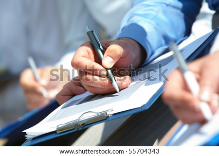 Human hand over paper making notes in working environment - stock photo