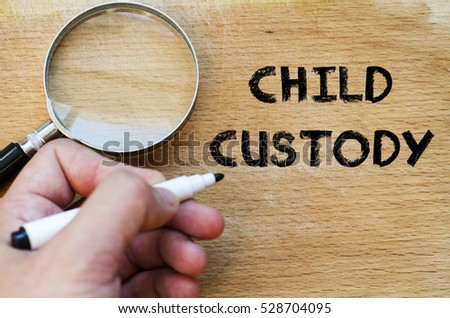 Human hand over wooden background and child custody text concept