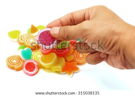 human hand pick up jelly sweet candy isolated on white background - stock photo