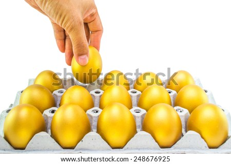 Human hand picking a gold egg from a tray: Concept of a golden egg opportunity for a chance for fortune and wealth: World food day: Prosperity retirement & investment concept: Chinese new year food - stock photo