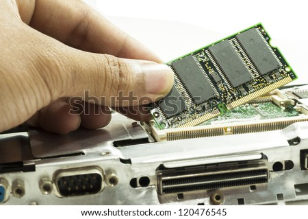 Human hand placing the RAM memory card on laptop computer motherboard - stock photo