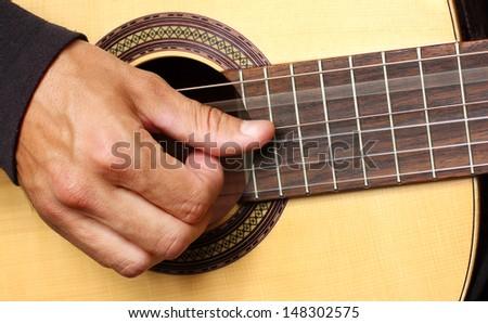 human hand playing guitar, vibrating string - stock photo