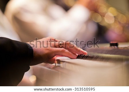 Human hand playing the synthesizer closeup - stock photo