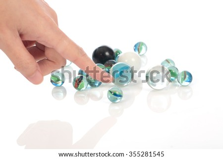 Human hand  point glass marbles balls on white blackground, selective focus - stock photo