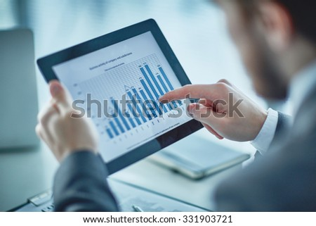 Human hand pointing at financial chart in digital tablet