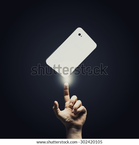 Human hand pointing at mobile phone with finger - stock photo