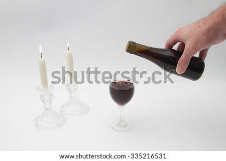 Human hand pours a glass of wine Kiddush the Shabbat, Shabbat candles Shabbat according to a table with a white tablecloth. - stock photo