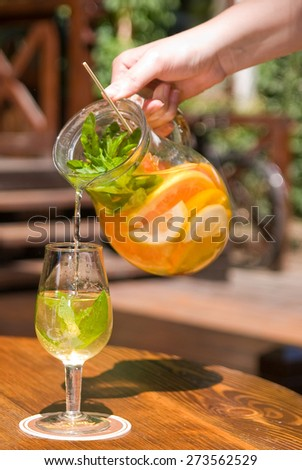 human hand pours a white sangria in the glass - stock photo