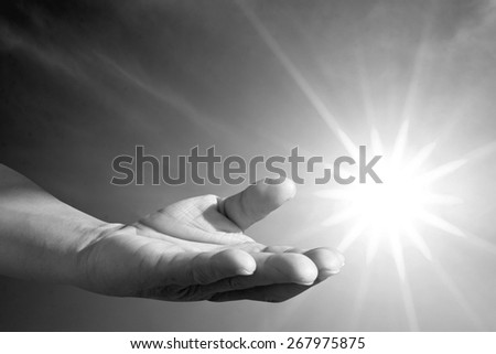 human hand praying over blur bright environment - stock photo