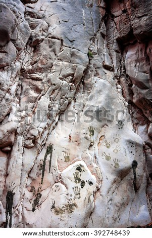 Human hand prints of mud on a mountain wall - stock photo