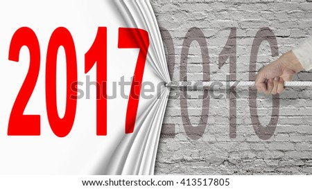 Human hand pulling 2017 white curtain covering 2016 on old brick wall background - stock photo