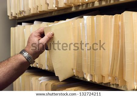 Human Hand Pulls File Folder off Shelf of Client Files - stock photo