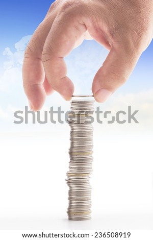 Human hand put coin to stack of coins over blurred world map of clouds background. Investment, Banking, Saving, Trust concept.