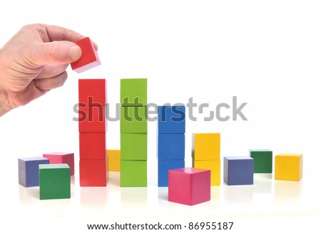 Human hand puts last block on abstract chart on white background