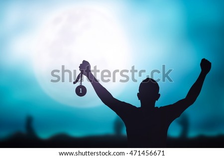 Human hand raised, holding gold medal against sky. Arm Win Goal First Moon Photo Prize Best Match Olympic Hero Metal Cloud Aim Green Blue Day Pride Crowd Banner Champ Badge Contest Place Night Super