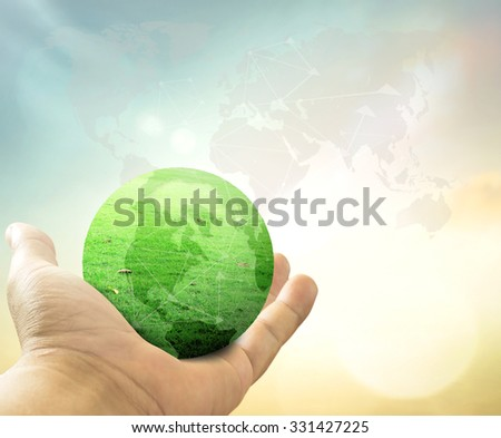 Human hand showing a green earth of grass over blurred world map of clouds on autumn sunset background. Give Life Humanitarian Ecological City Connection CSR Donation Investment concept - stock photo