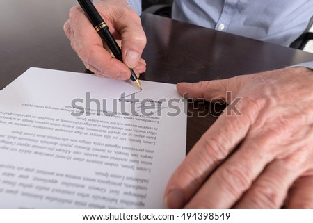 Human hand signing a contract