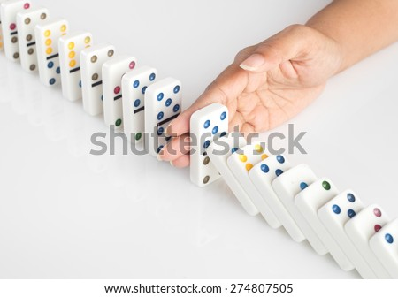 Human hand stopping a line of dominoes from falling. concept image for recovery plan and solution for cascading failures and problems. Dominoes are placed on a white table. High key image . - stock photo