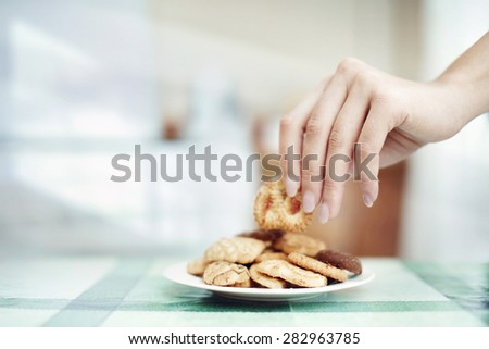 Human hand taking cookie in plate on a table - stock photo