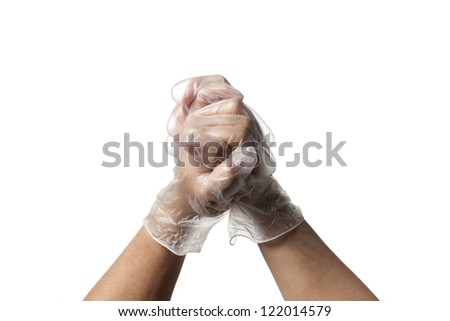 Human hand together while wearing transparent surgical gloves.
