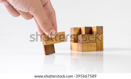 Human hand touching and assembling wooden cube puzzle. Isolated on white background. Slightly de-focused and close-up shot. Copy space.
