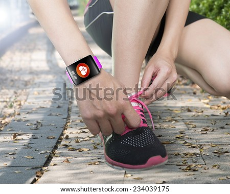human hand tying shoelaces wearing bright pink watchband touchscreen smartwatch with red health icon on forest trail background - stock photo