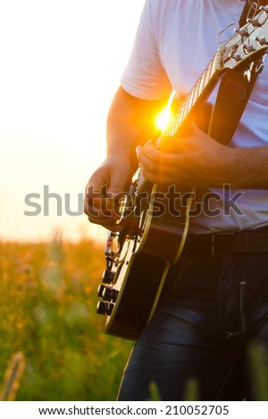 Human hand with a guitar in the rays of the setting sun  - stock photo