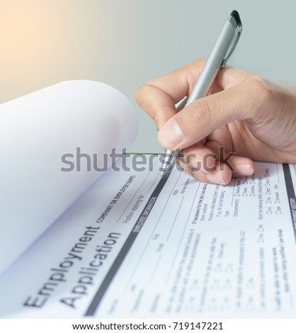 human hand with ballpoint pen over application form