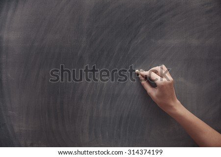Human hand with chalk at the blackboard - stock photo