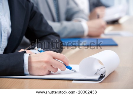 Human hand with pen over paper ready to write something