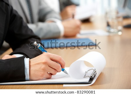 Human hand with pen over paper ready to write something - stock photo