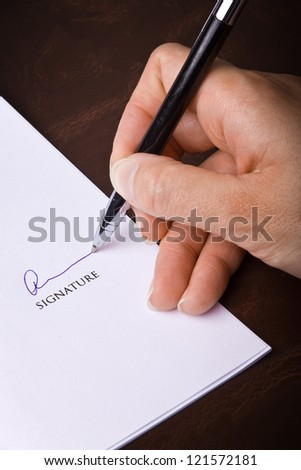 Human hand with pen signing a document - stock photo