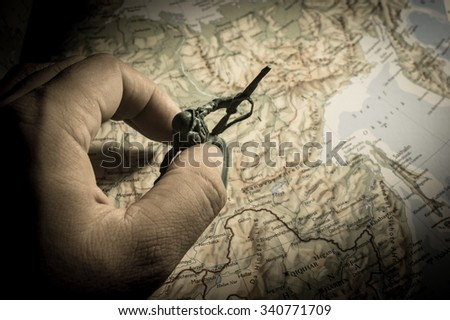 Human hand with soldier toys on map - stock photo